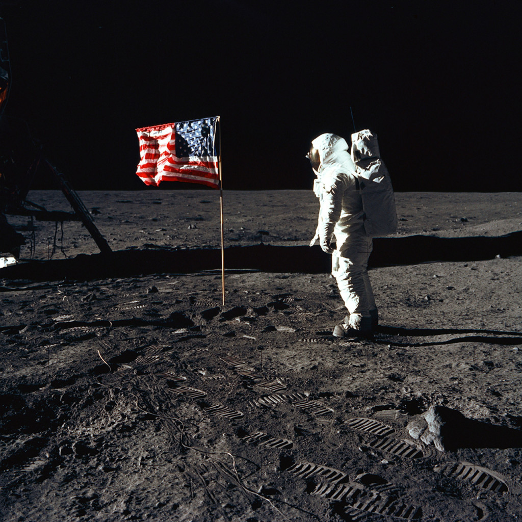 """Astronaut Buzz Aldrin, lunar module pilot of the first lunar landing mission, poses for a photograph beside the deployed United States flag during an Apollo 11 Extravehicular Activity (EVA) on the lunar surface. The Lunar Module (LM) is on the left, and the footprints of the astronauts are clearly visible in the soil of the Moon. Astronaut Neil A. Armstrong, commander, took this picture with a 70mm Hasselblad lunar surface camera. While astronauts Armstrong and Aldrin descended in the LM, the """"Eagle"""", to explore the Sea of Tranquility region of the Moon, astronaut Michael Collins, command module pilot, remained with the Command and Service Modules (CSM) """"Columbia"""" in lunar-orbit."""